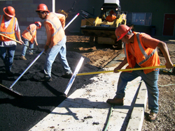 Skillful lute operators completing a smooth mat asphalt finish